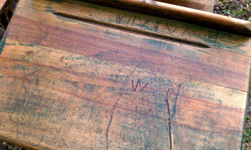 names carved into antique wooden school desk