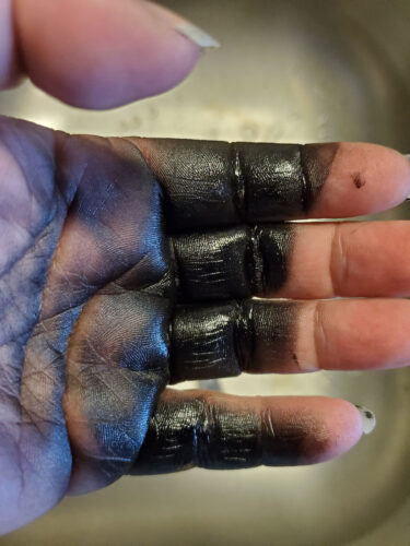 black spray paint on hand